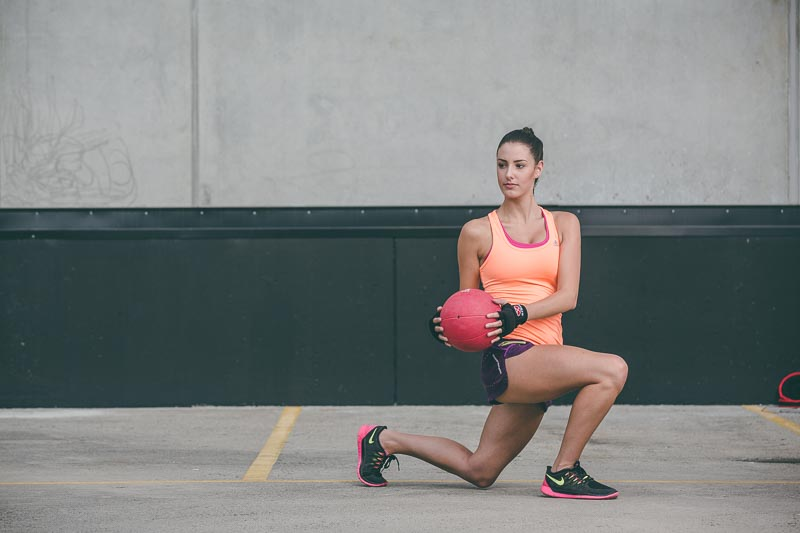 Image of Tayla lunging with a medicine ball | Profoto HSS flash fired